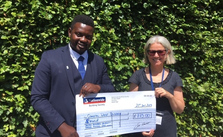 Young man in suit holds giant cheque with West Sussex Mind CEO