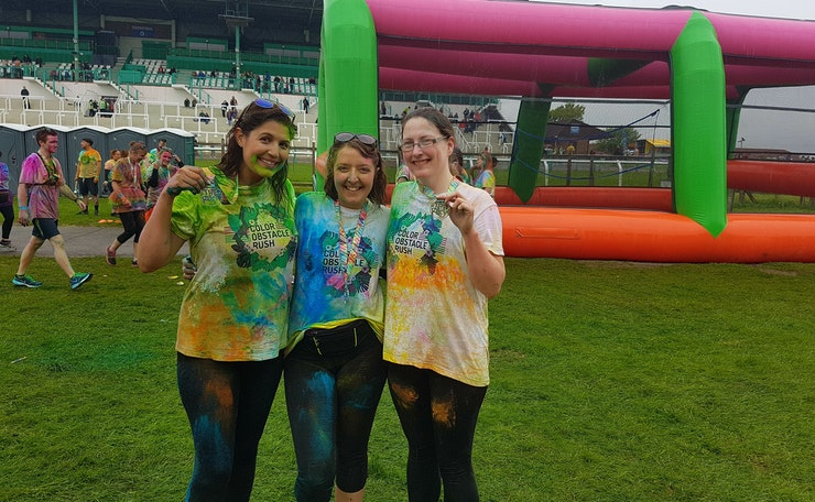 Three women in T-shirts splashed with paint happily hold up medals at outside event