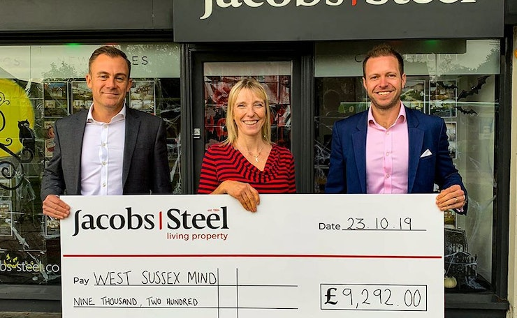 Two men and a woman smile and hold a giant cheque in front of estate agent window