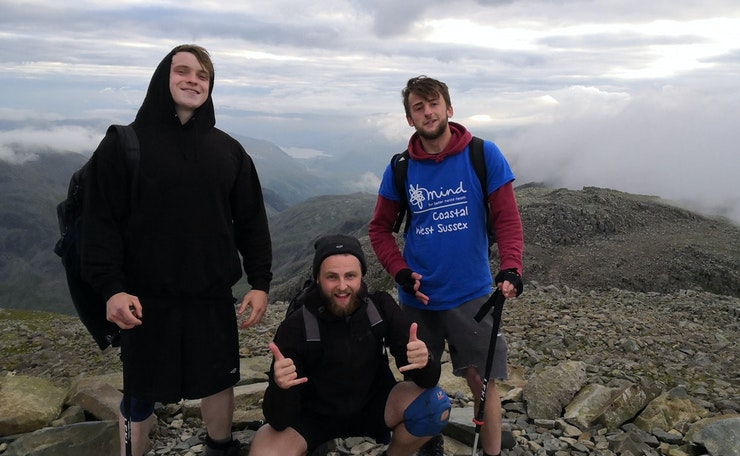 Three young men, one in West Sussex Mind T-shirt, at the top of a mountain