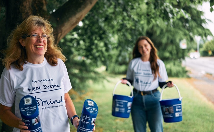 Two women in supporters' T-shirts hold collection tins and buckets with trees behind