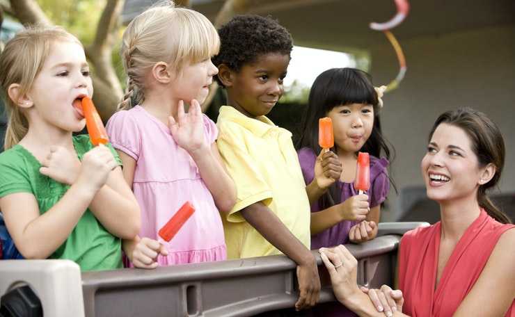 Four pre-school children eat ice lollies with young woman, at outside event