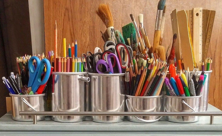 Pots with brushes, pencils, scissors, rulers