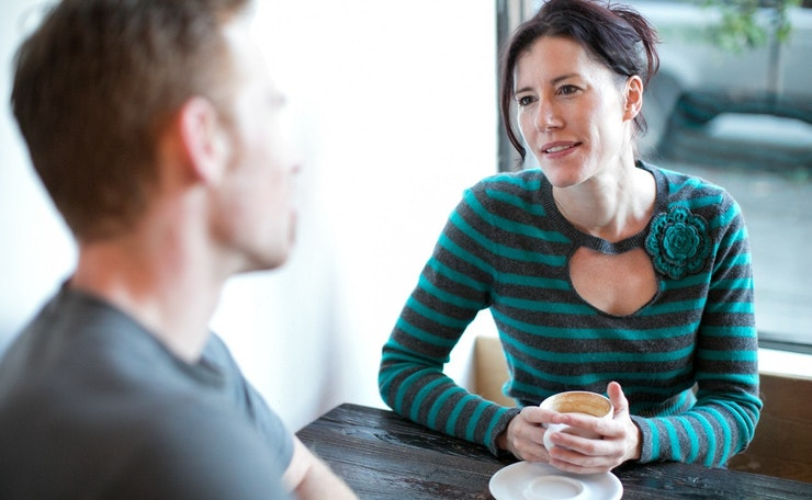 Woman listening to man over cup of coffee