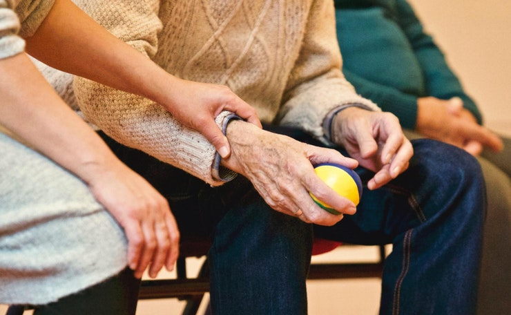 Woman's hand is supportively on elderly man's arm as he holds a ball
