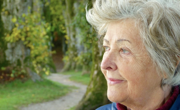 Older woman looks to the side with greenery behind