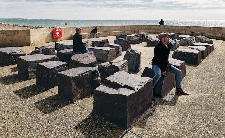 james sits on rocks at beach