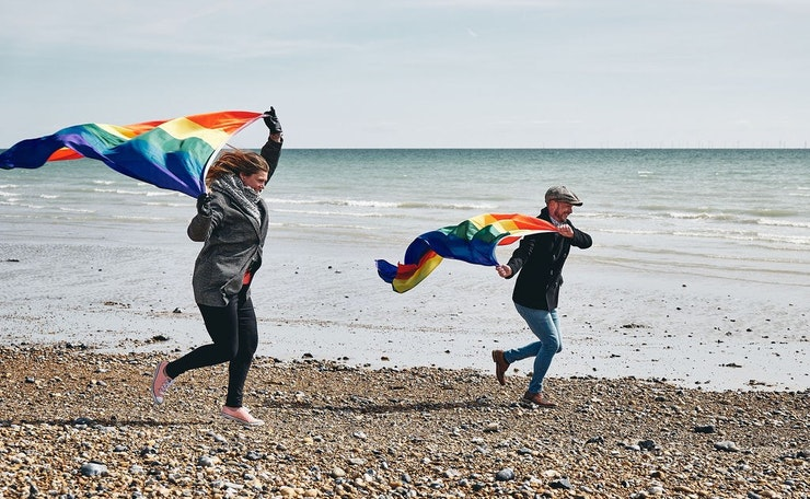 Two run along beach with flags in the wind