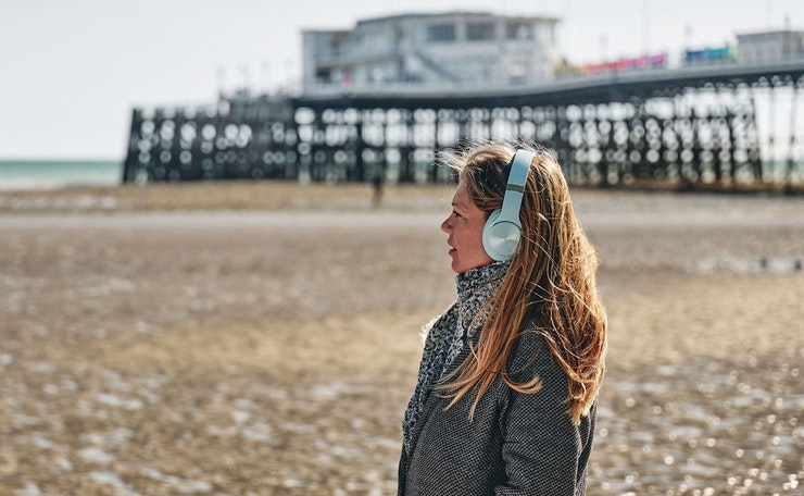 keira with headphones, pier in background