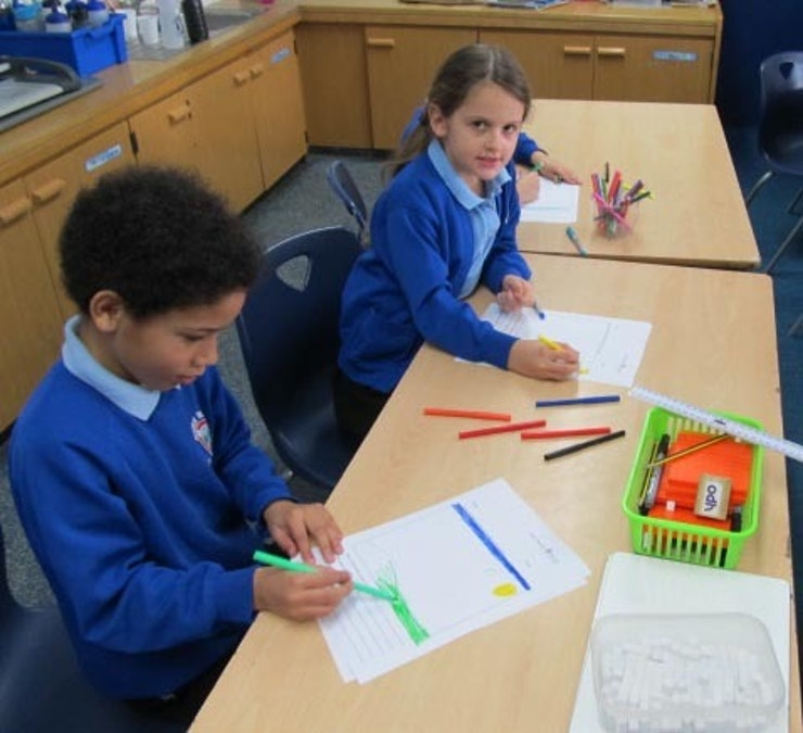 Small boy and girl at school table drawing their designs