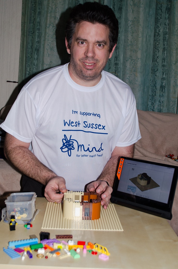 Stephen, in supporter's T-shirt uses lego