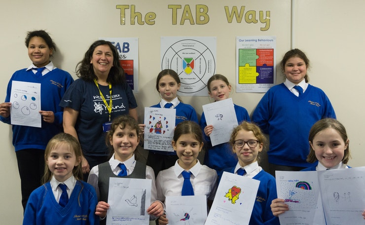 Louisa Hernandez with group of pupils holding up their designs