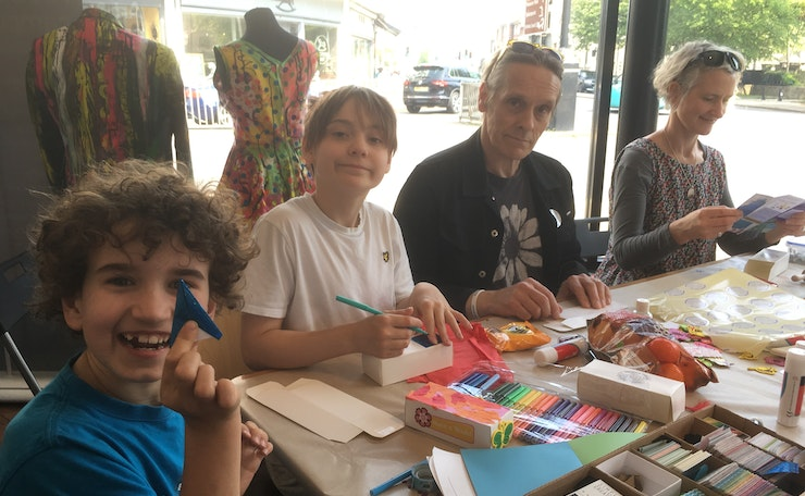 Two children and two adults at table with crafts to create well-being boxes