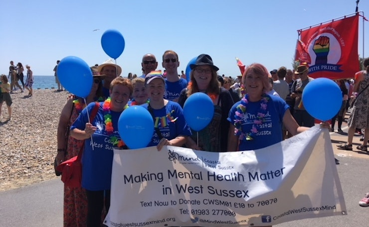 Group of people with West Sussex Mind banner and balloons on seafront at Worthing
