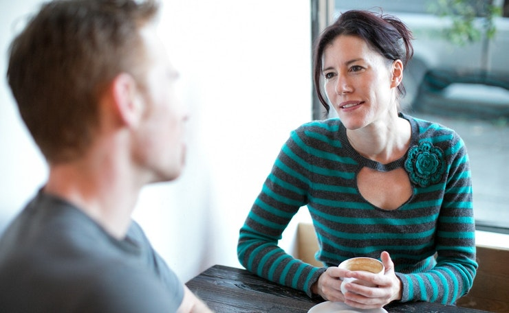 Woman and man sitting at table and talking over cup of coffee
