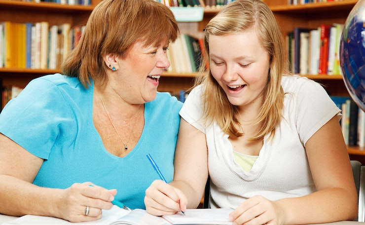 Happy woman and teenage girl at table in library with notebooks and pens