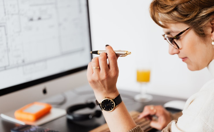 woman at computer with raised pen